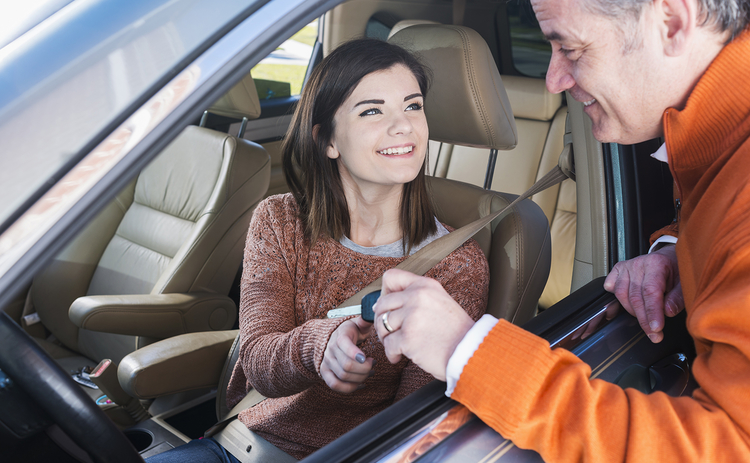 Father giving daughter key to car