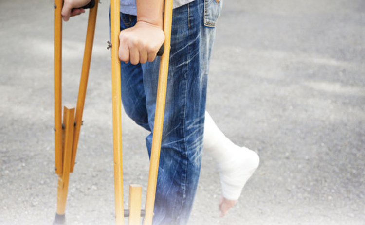 A person on crutches with their leg in plaster