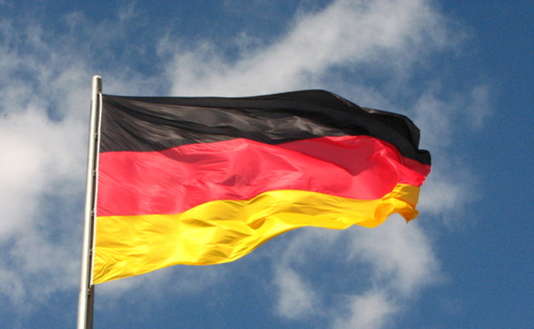 German flag flying in a blue sky