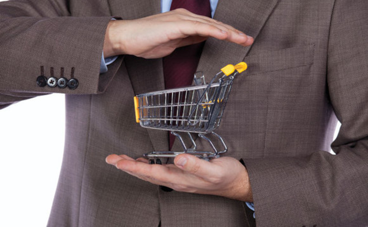 A miniature shopping trolley being cradled in the hands of a suited man