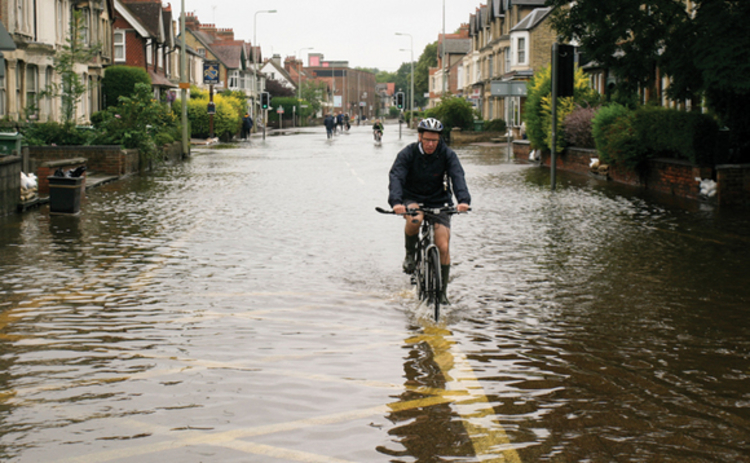 Cyclist riding through flooded road