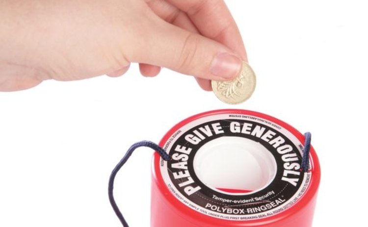 A pound coin being placed into a charity tin