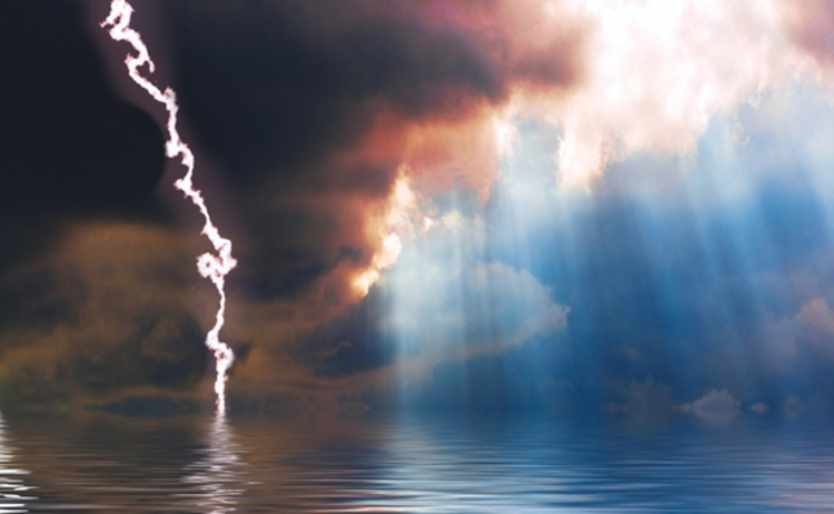 Dark storm clouds and lightning broken by the sun shining down onto a calm sea