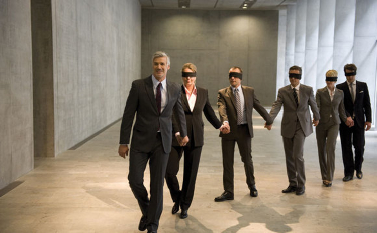 A businessman leading blindfolded colleagues