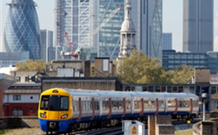 Train leaving London with City skyline behind