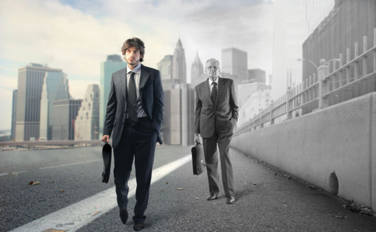 A young businessman walking ahead of an older businessman