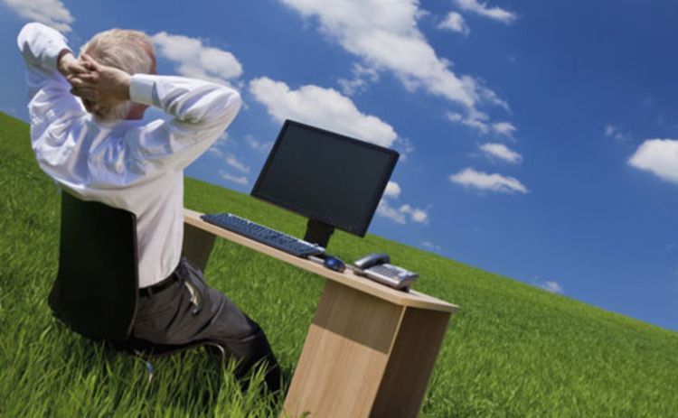A man using his desktop in a field and looking at clouds