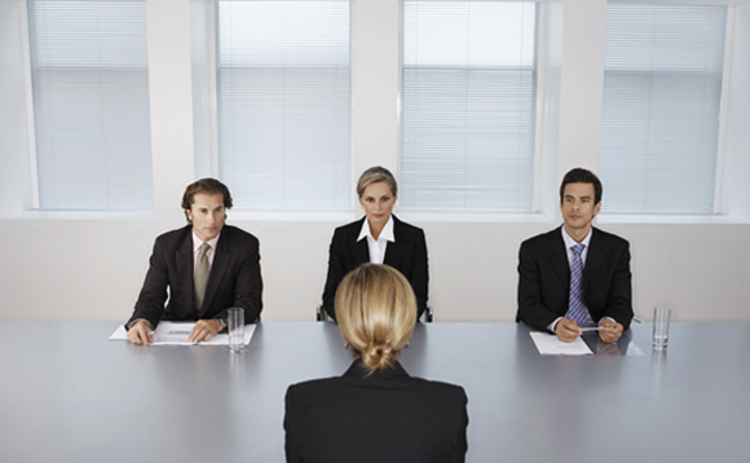 Photo of a woman facing a three-person interview panel