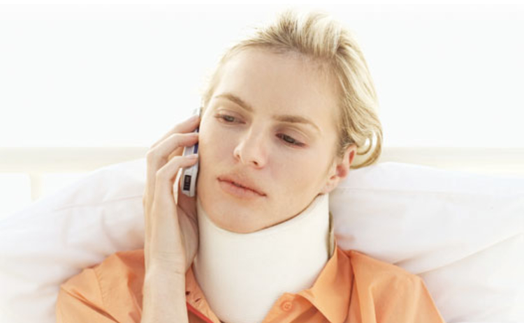 A woman with whiplash talking on the phone