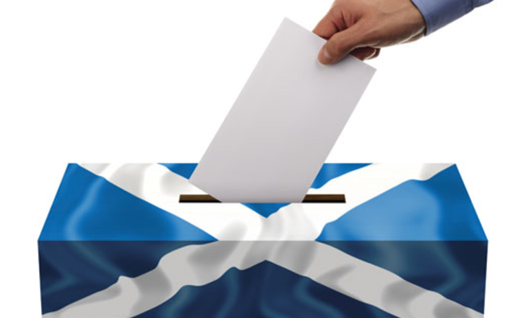 A hand putting a voting slip into a box adorned with the Scottish flag denoting the Scottish independence referendum