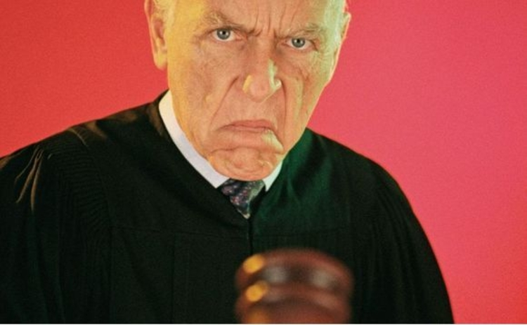 Judge with stern expression pointing gavel
