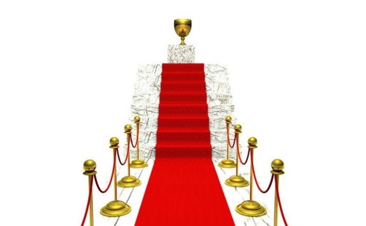 Cordoned off red carpet up stairs leading to gold trophy