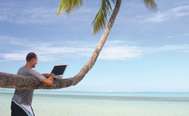 A man working with a laptop on the beach