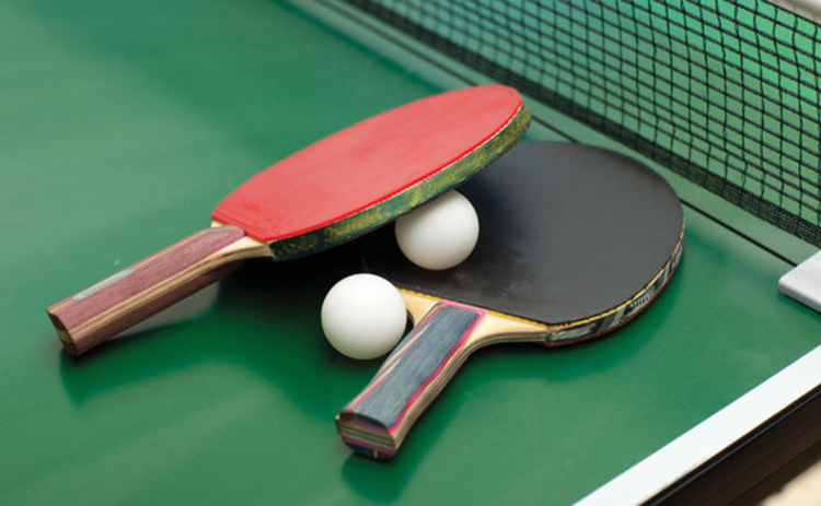 Two table tennis paddles and balls on a ping pong table