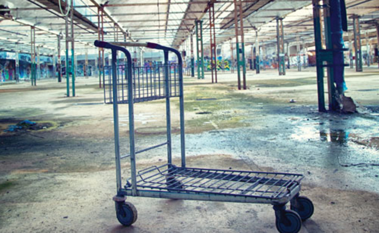 An unoccupied warehouse building with an abandoned trolley in it