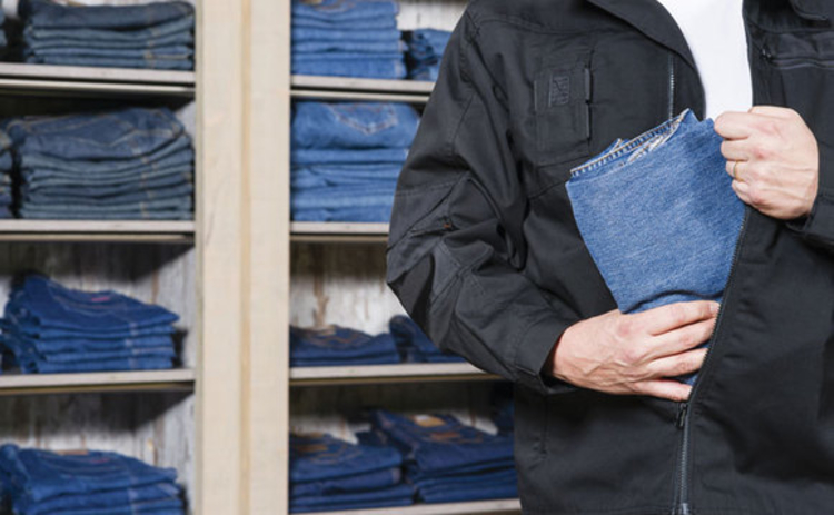 A man stealing jeans from a shop by hiding them in his jacket