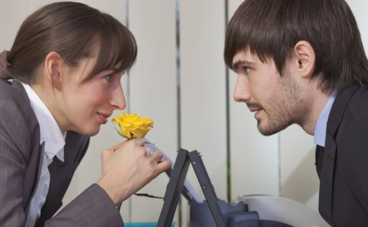 Man and woman exchanging a flower