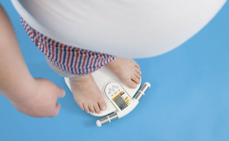 An obese man standing on weighing scales